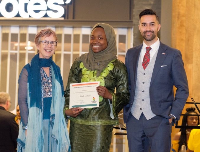 Picture of young muslim student being awarded a scholarship by community leaders in Hamilton