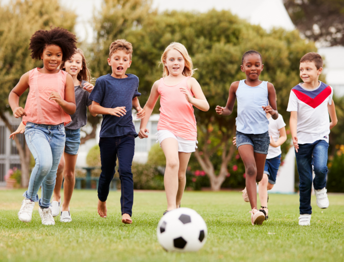 Picture of a group of diverse young kids running after a soccer ball in a playground